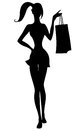 Silhouette of beautiful girl with shopping bags in hand