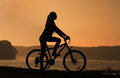 Silhouette of a bike young girl sitting on the by the river at sunset Royalty Free Stock Photography
