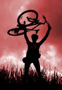 Silhouette of a biker holding his bicycle Royalty Free Stock Photo