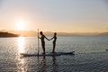Silhouette of boy and girl on sup surf pull hands together at the ocean. Concept lifestyle, sport, love Royalty Free Stock Photo