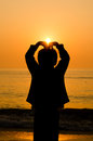 Silhouette boy hand making a heart shape with sunrise on the beach Stock Photos