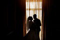 Silhouette of a bride and groom on the background of a window wi