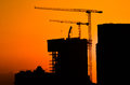 Silhouette of building under construction and the construction crane or power crane sunset time. Royalty Free Stock Photo