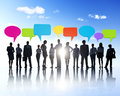 Silhouette of business people standing horizontally group with multi colored speech bubbles above them Stock Images
