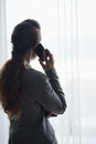 Silhouette of business woman talking cell phone and looking into window Stock Image