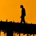 Silhouette of construction workers on scaffold working under a hot sun Royalty Free Stock Photos