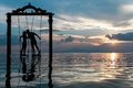 Silhouette of Couple Kissing Standing on Swing in Calm Sea during Sunset