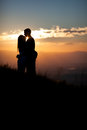 Silhouette of couple kissing in sunset on mountain Stock Image