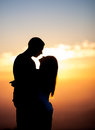 Silhouette of couple kissing in sunset on mountain Stock Photo