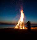 Silhouette of a couple in love against fire background romantic evening on the beach Stock Photo