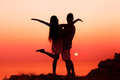 Silhouette couple in love they stand on a cliff by the sea at sunset Royalty Free Stock Photo