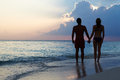 Silhouette of couple walking along beach at sunset holding hands Royalty Free Stock Photography