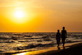 Silhouette of couple walking on the beach. Royalty Free Stock Photo