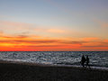 Silhouette couples walking along sunset beach Royalty Free Stock Photo