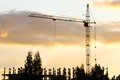Silhouette of crane and building under construction in evening at sunset Stock Photos