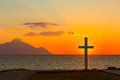 Silhouette of cross at sunrise or sunset with light rays and sea panorama Royalty Free Stock Photo