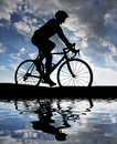 Silhouette of the cyclist riding a road bike at sunset Stock Photos