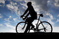 Silhouette of the cyclist on road bike at sunset Stock Photography