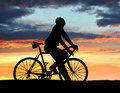 Silhouette of the cyclist on road bike at sunset Stock Photo