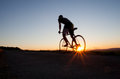 Silhouette of cyclist in sunset sky Stock Image