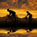Silhouette of the cyclists riding a road bike at sunset Stock Photo