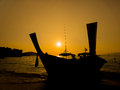 Silhouette dark longtail boat on the beach over sunset Stock Photo