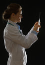 Silhouette of doctor woman knocking on syringe Royalty Free Stock Photography