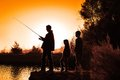 Silhouette family fishing a outing outdoors children looking on while father is Royalty Free Stock Photography