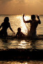 Silhouette of family having fun in sea on beach holiday playing Stock Photos