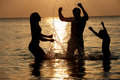 Silhouette of family having fun in sea on beach holiday playing Stock Photography