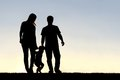 Silhouette of Family of Three People Walking at Sunset Royalty Free Stock Photo