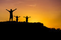 Silhouette father children standing raised hands up on sunset. Royalty Free Stock Photo