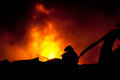 Silhouette of firemen fighting a raging fire with huge flames burning timber Stock Images