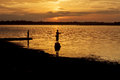 Silhouette fisherman of Lake in action when fishing. Royalty Free Stock Photo