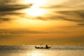 Silhouette of fishermen in the boat on sea with yellow and orange sun in the background Royalty Free Stock Photo
