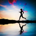 Silhouette fit woman running sunset water reflection Royalty Free Stock Photo