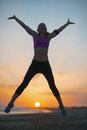 Silhouette of fitness young woman jumping on beach at dusk sandy Stock Photography