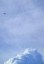 Silhouette of a flying airplane on bright blue cloudy sky with cumulus clouds at below Royalty Free Stock Photo