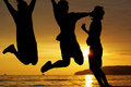 Silhouette friends jumping on the beach Stock Photography