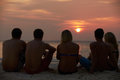 Silhouette of friends sitting on beach watch the sun set Royalty Free Stock Photos
