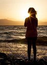 Silhouette of a girl at the beach at sunset in summer evening Stock Image