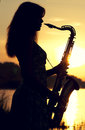 Silhouette of a girl in a dress with a brass musical instrument in his hands looking thoughtfully into the distance