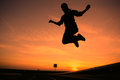 Silhouette of a girl jumping sunset Royalty Free Stock Photos