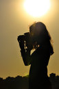 Silhouette of girl in shooting time isolated on sunset background Royalty Free Stock Images