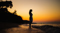 A silhouette of a girl standing in the sea on the sunset beautiful Royalty Free Stock Images