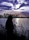 Silhouette of girl walking on the lakeside there is mysterious landscape around picture looks unusual and expressive Royalty Free Stock Photos