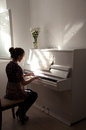 Silhouette of the girl who plays the white piano Royalty Free Stock Photo