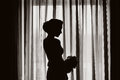 Silhouette of a girl at the window Stock Photography