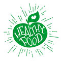 Silhouette of a green apple with heart and lettering text Healthy Food. Vector color label