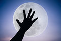 Silhouette of a hand with large full moon on fantastic sky background.